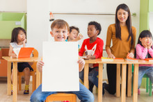 Cute Boy Holding Blank White Poster With Happy Face In Kindergarten Classroom, Kindergarten Education Concept, Vintage Effect Style Pictures.