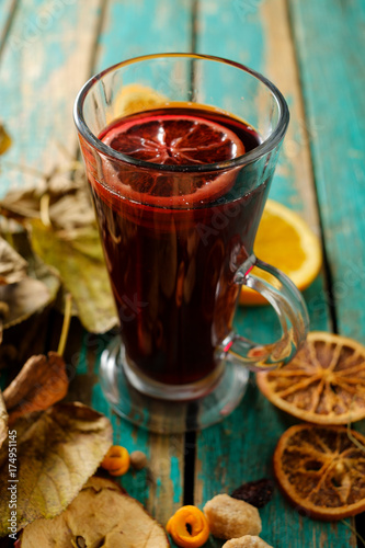 Obraz na plátně Hot mulled wine with orange, cinnamon, cardamom and anise on green wooden backgr
