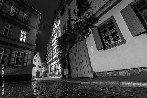 Fotobehang Smal steegje Enge Gasse in Erfurt in der Nacht (schwarzweiss)