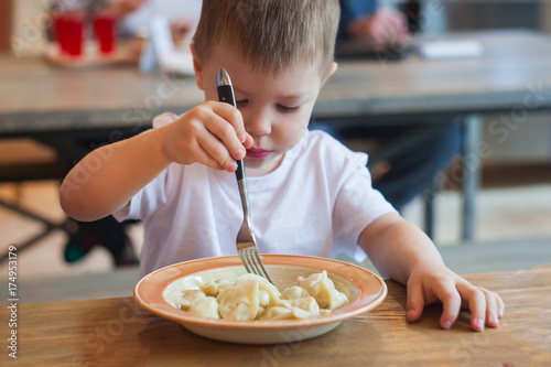 Zdjęcie XXL zabawny chłopczyk jedzenie w kawiarni, jedzenie koncepcja