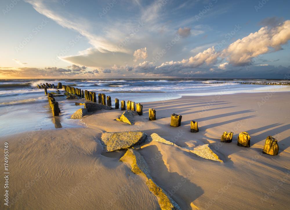 Fototapeta a sea breakwater breaking the waves at sunset