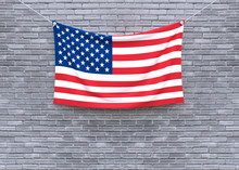 American Flag Hanging On Brick...