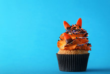 Halloween Cupcake With Sprinkles And Candies On Blue Background