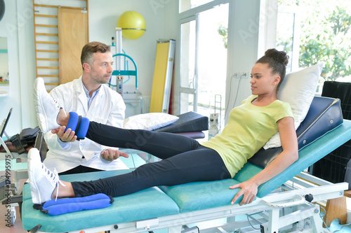 Fotografía  doctor is stretching woman leg on physiotherapy session