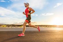 Triathlon - Triathlete Man Running In Triathlon Suit Training For Ironman Race. Male Runner Exercising On Big Island Hawaii. Sunset.