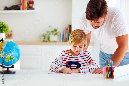 Zdjęcie XXL ojciec i syn przy biurku, kształcący się w domu