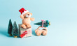 Small teddy bear in a Santa hat with a present box and Christmas trees