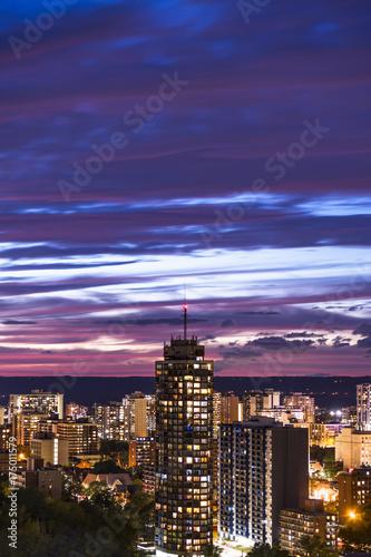 Fotografía  Tall building and vibrant illuminated city beneath a dark blue and pink sunset s