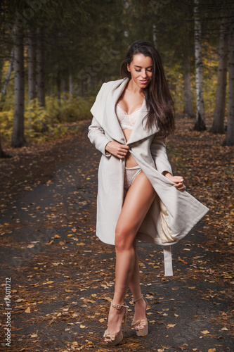 25e88defc Young beautiful dark-haired woman with a slender figure posing positively  in white lingerie and a classic coat in an autumn park