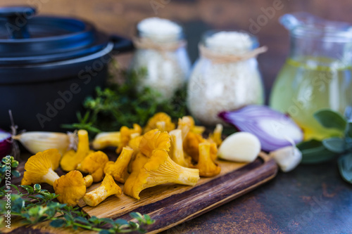 Ingredients for preparing risotto, Italian food. Fresh chanterelle mushrooms with arborio and herbs.