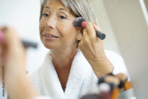 Plakat Starsza kobieta przed lustrzanym kładzenia makeup dalej