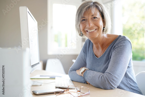 Photo  Portrait of mature businesswoman working on desktop