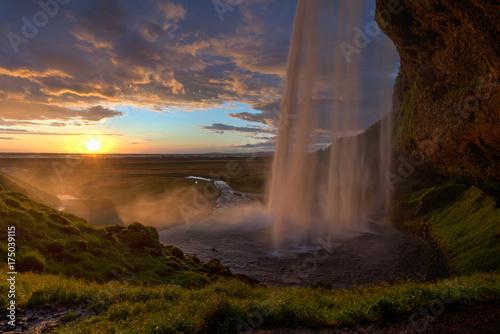 Foto op Canvas Watervallen Blick hinter dem Wasserfall zum Sonnenuntergang