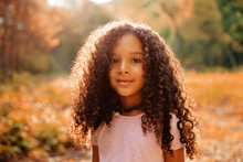 Outdoor Portrait Of A Cute Afro American Happiness Little Girl With Curly Hairl.