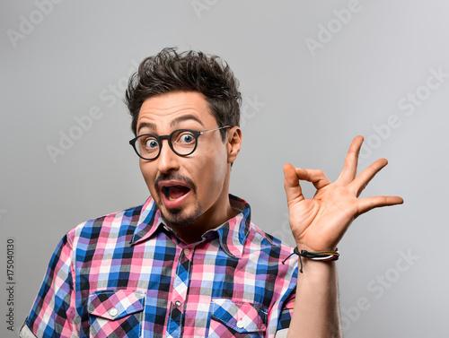 Fototapeta Przystojny młody człowiek Zabawa Szalony. Zaskoczony gest, otwarte usta. Portret Hipster nerd facet w modnej koszuli, okulary. Brunetki Brodata Emocjonalna Elegancka fryzura na szarym tle. Niebieskie oczy