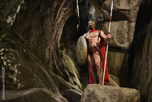 Naklejki Gladiator confident-anonymous-man-with-muscular-body-holding-weapon-and-shield-while-posign-in-gladiator-outfit-on-rocks-spartan