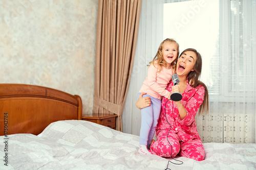 Plakat Matka i córka śpiewają razem piosenki karaoke w pokoju. Szczęśliwa rodzina.