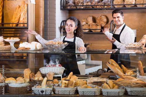Deurstickers Bakkerij Cheerful couple selling pastry and loaves