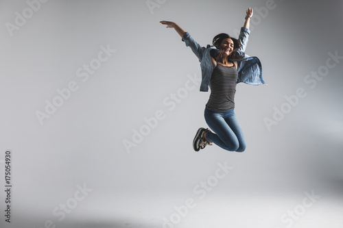Photo  Playful young woman wearing casual jumping over grey background