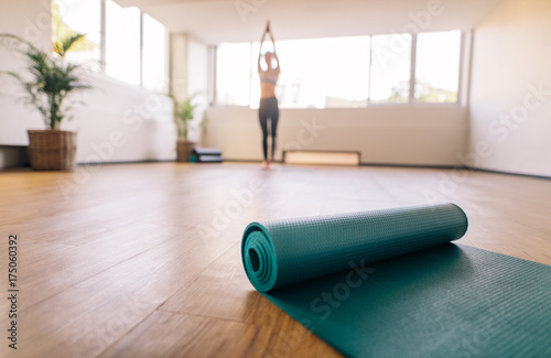 Tuinposter School de yoga Exercise mat on floor with woman doing yoga