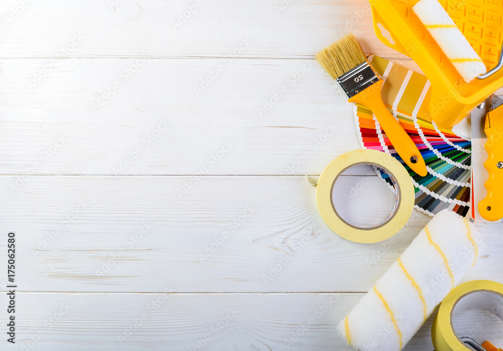 Fototapety, obrazy: Mock up of color samples catalog, brush, adhesive tape and paint rollers, different painting tools on light wooden background. Concept of renovation, choosing and major repair, top view