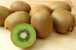 Heap of fresh ripe kiwi fruits, both whole fruits and cross-sections, on the wooden table