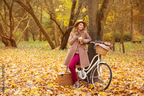 Fototapeta travel concept young woman walk with bicycle picnic set hot drinks in bright autumn city park background copy space  obraz na płótnie
