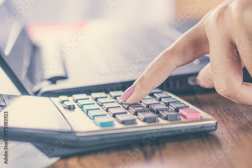 Pinturas sobre lienzo  business woman hand counting on calculator with blur background of computer lapt