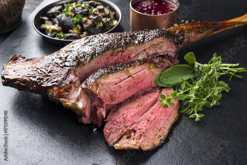 Barbecue haunch of venison with mushrooms and cranberry sauce as close-up on a slate slab