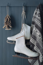 Ice Skates With Blanket And Christmas Tee Ornament On Hooks