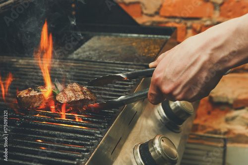 Canvastavla Man cooking meat steaks on professional grill outdoors