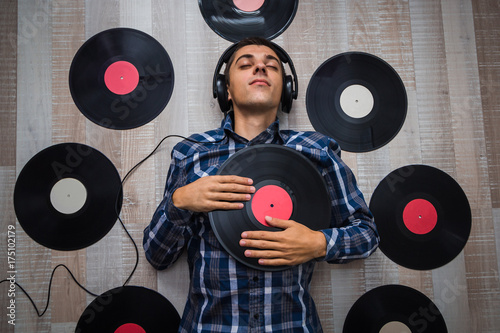 Photo top view man (music lover) with headphones lie on the floor and listen music amo