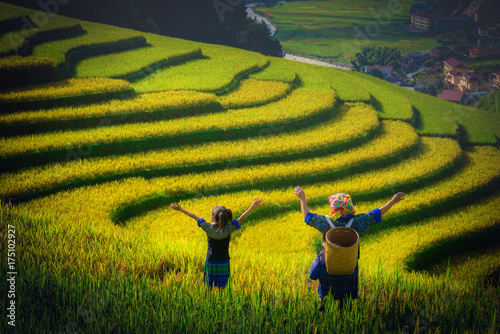 Women farmer and daughter raising armม on Rice fields terraced at sunset in Mu Cang Chai, YenBai, Vietnam.