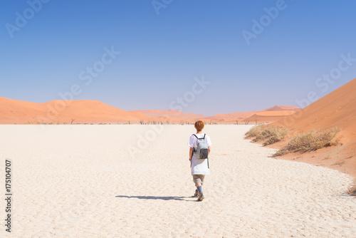 Poster Jogging Tourist walking on the scenic dunes of Sossusvlei, Namib desert, Namib Naukluft National Park, Namibia. Adventure and exploration in Africa.
