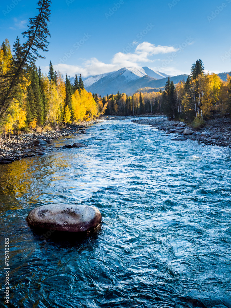 River view in autumn time with stone foreground, in Hemu village, Xinjiang, China.