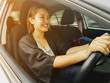Young Asian Woman driving a car. Side view of young girl driving a car while Not wearing seatbelts
