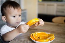 A Child Takes Slice Of Orange