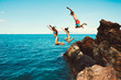 canvas print picture - Friends cliff jumping into the ocean