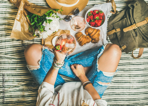 Keuken foto achterwand French style romantic picnic setting. Woman in jeans with glass of rose wine, fresh strawberries, croissants, brie cheese, sunglasses, peony flowers on blanket, top view. Outdoor gathering concept