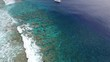 Tilt up, aerial of sailboat off coast of tropical island