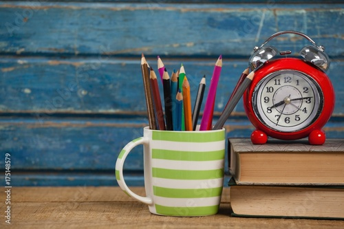 Fototapeta  Alarm clock, books and pen holder
