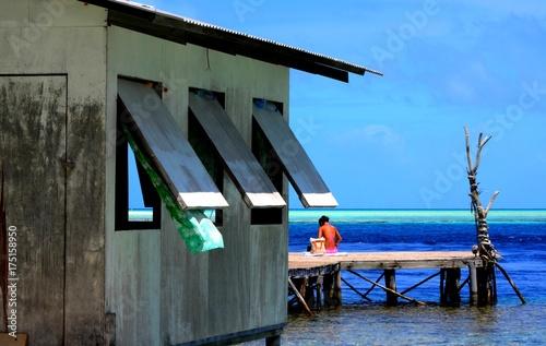 Photo cabane de pêcheur avec fille qui prend le soleil sur ponton polynésie française