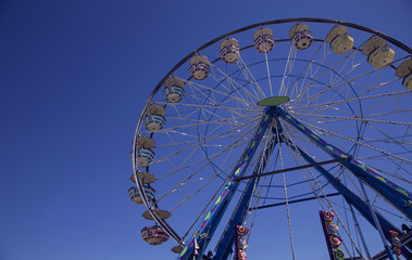 Isolated Upward Frontal View of Ferris Wheel Against Deep Blue Sky