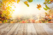 canvas print picture - Wooden table with autumn leaves background