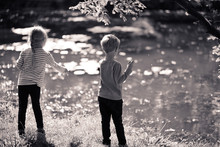 Little Girl And Boy Feed Ducks On The Pond