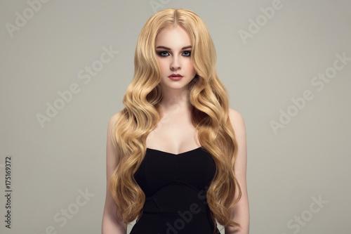 Fényképezés  Blond woman with long curly beautiful hair.