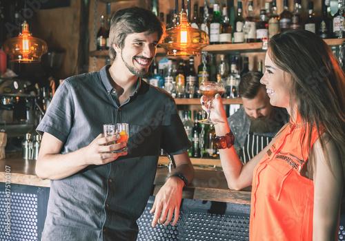 Drunk man sitting at bar, drinking cocktail, looking at girls Fototapet