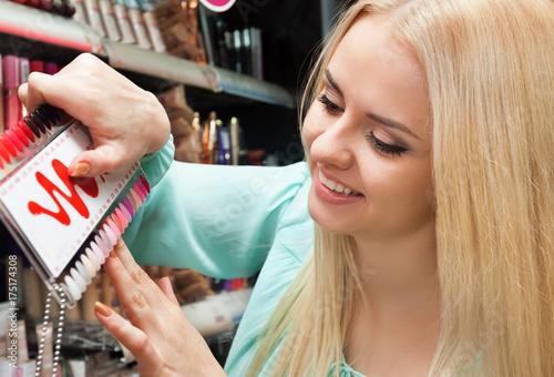 Plakat blond dziewczyna wybiera kolor lakieru do paznokci