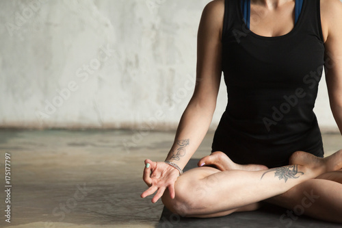 Young woman with tattoo practicing yoga, sitting in Padmasana exercise, Lotus pose, mudra gesture, working out, wearing sportswear, black shorts, top, indoor closeup image, wall background, copy space