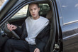 Young man in gray sweatshirt in car. Mock-up.